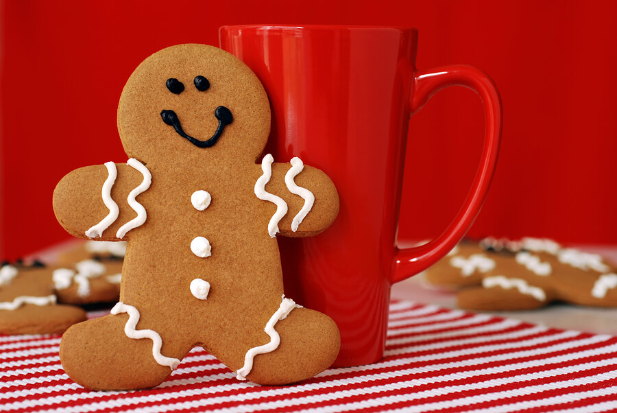 Smiling gingerbread man with red funnel mug. Additional cookies