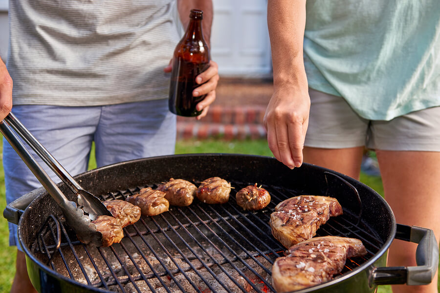 Women seasoning meat on outdoor garden barbecue while man turns