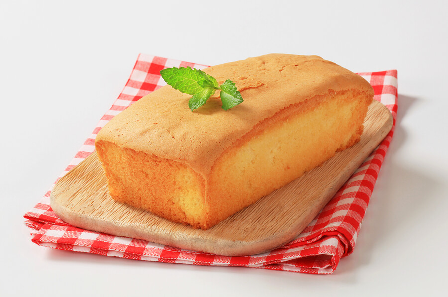 loaf of pound cake on wooden cutting board