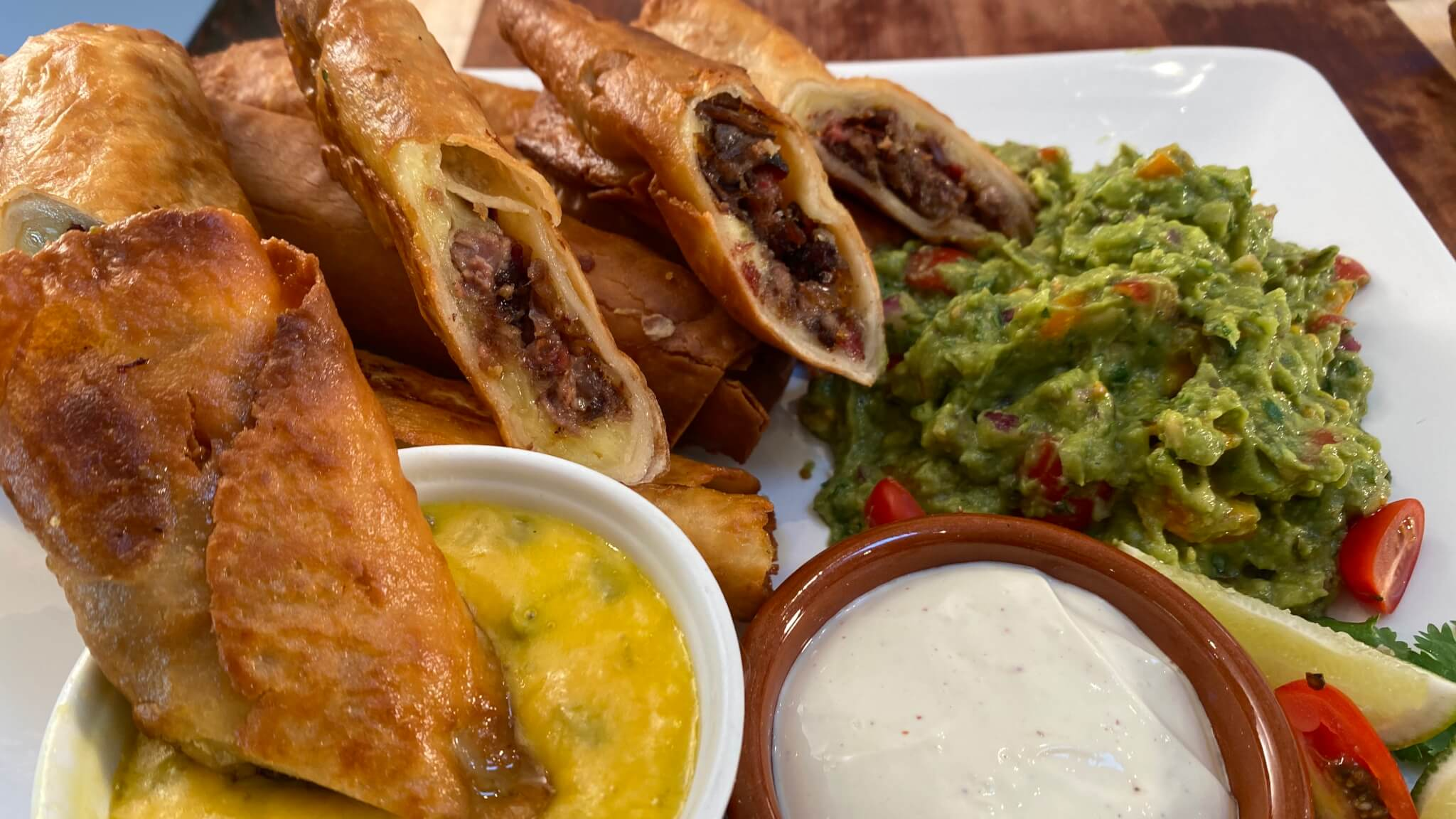Smoked Brisket Taquitos with Fresh Guacamole and Spicy Cheese Sauce